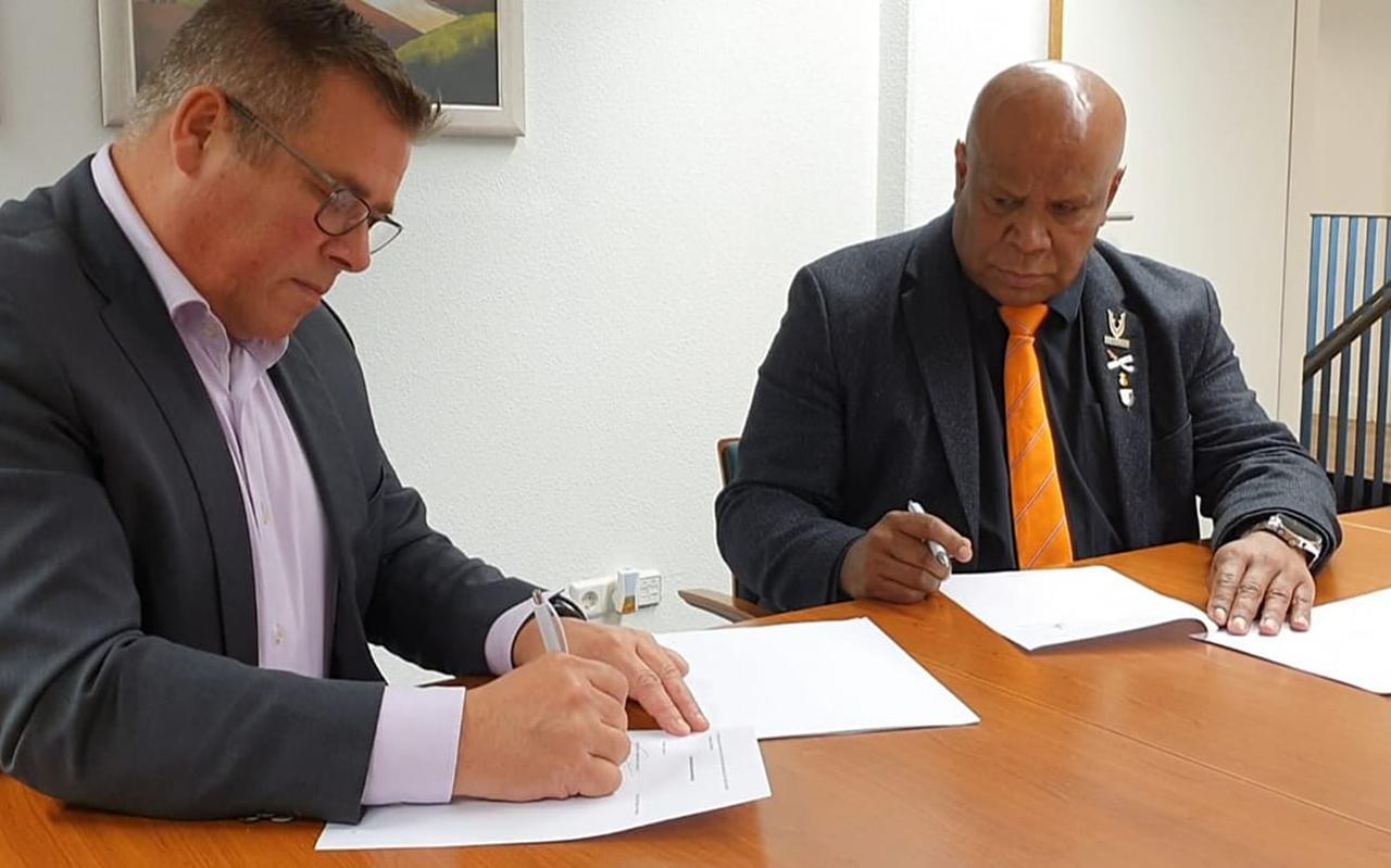 Directeur Ludy de Vos van het Veteraneninstituut (links) en Leo Reawaruw tekenen de intentieverklaring Veteranen en Familie orgprogramma KNIL-Ambonezen.