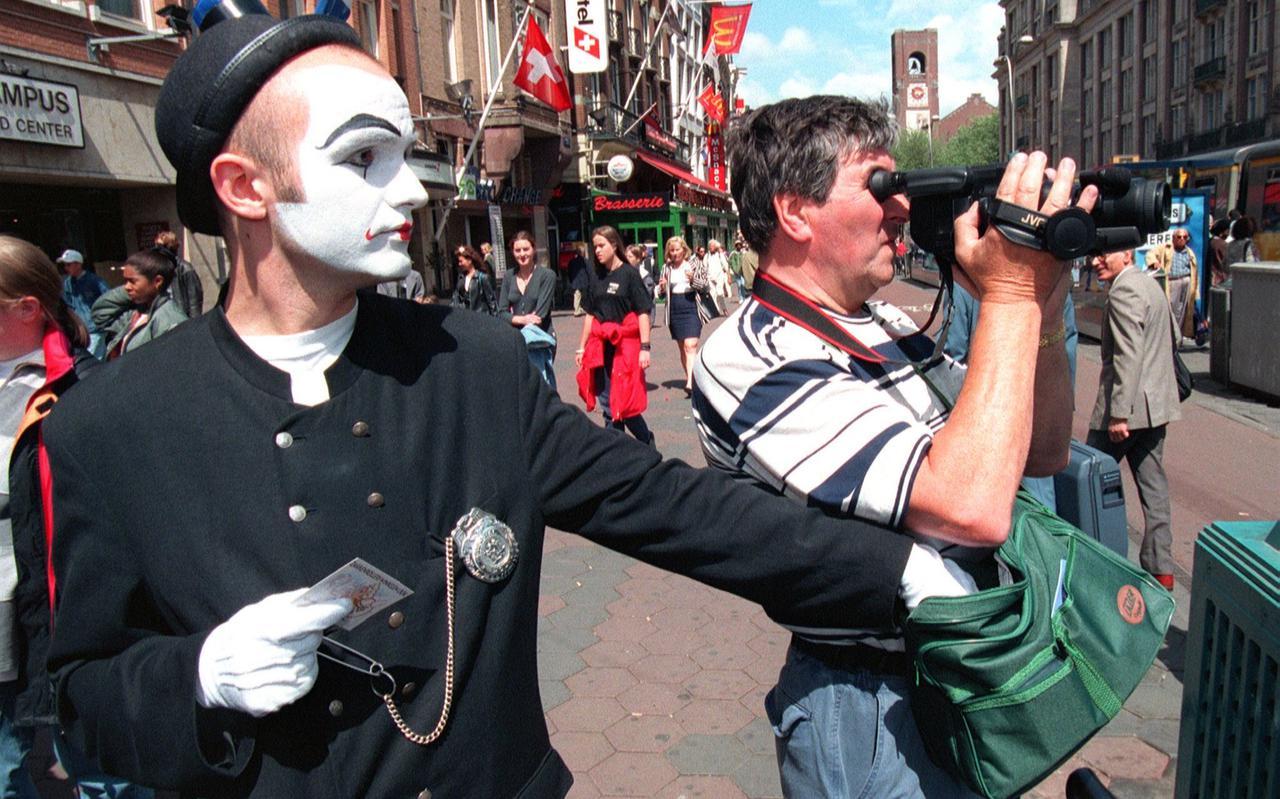 Een mimespeler (in dienst van de politie) rolt de tas van een toerist die rustig bezig is met zijn videocamera. Na zijn daad geeft hij de gerolde voorwerpen weer terug met een waarschuwing erbij.