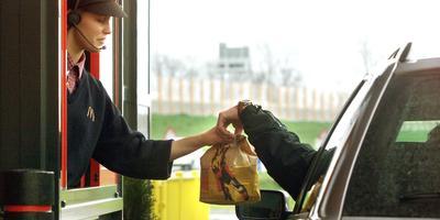 Een automobilist pikt zijn maaltijd op in een McDrive. FOTO ARCHIEF DVHN