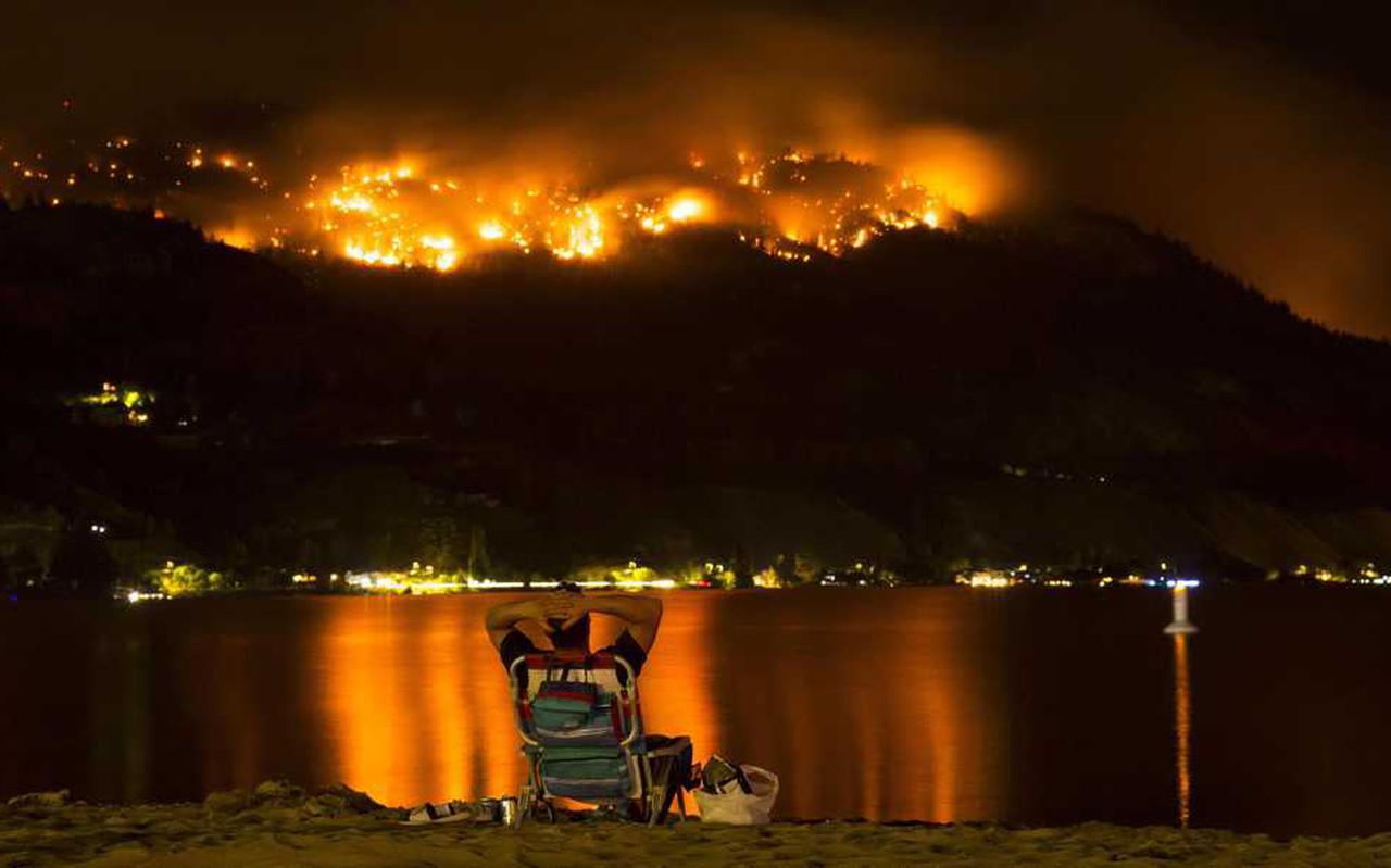 Een man kijkt naar de bosbranden in de westelijke provincie British Columbia in Canada.