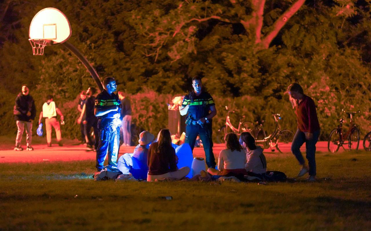 De politie spreekt feestende jongeren in het Noorderplantsoen aan.