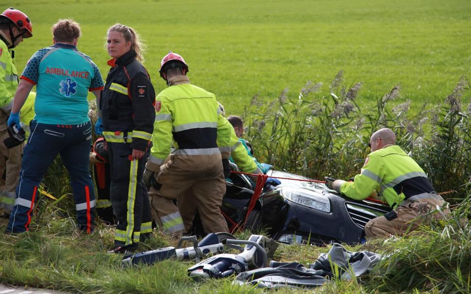 Auto belandt in sloot na aanrijding op Friesestraatweg bij Aduard. Brandweer bevrijdt inzittenden.