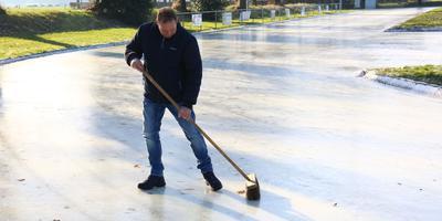 IJsmeester Kars Kroeze van ijsvereniging De Hondsrug uit Noordlaren is druk bezig de baan in perfecte conditie te krijgen. Foto: Van Oost Media