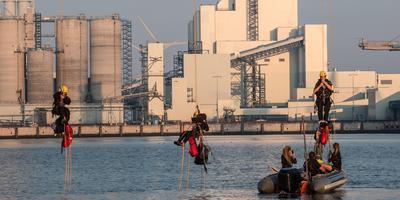 Greenpeace-activisten klimmen in de versperring. FOTO: MATTHIJS SORGDRAGER