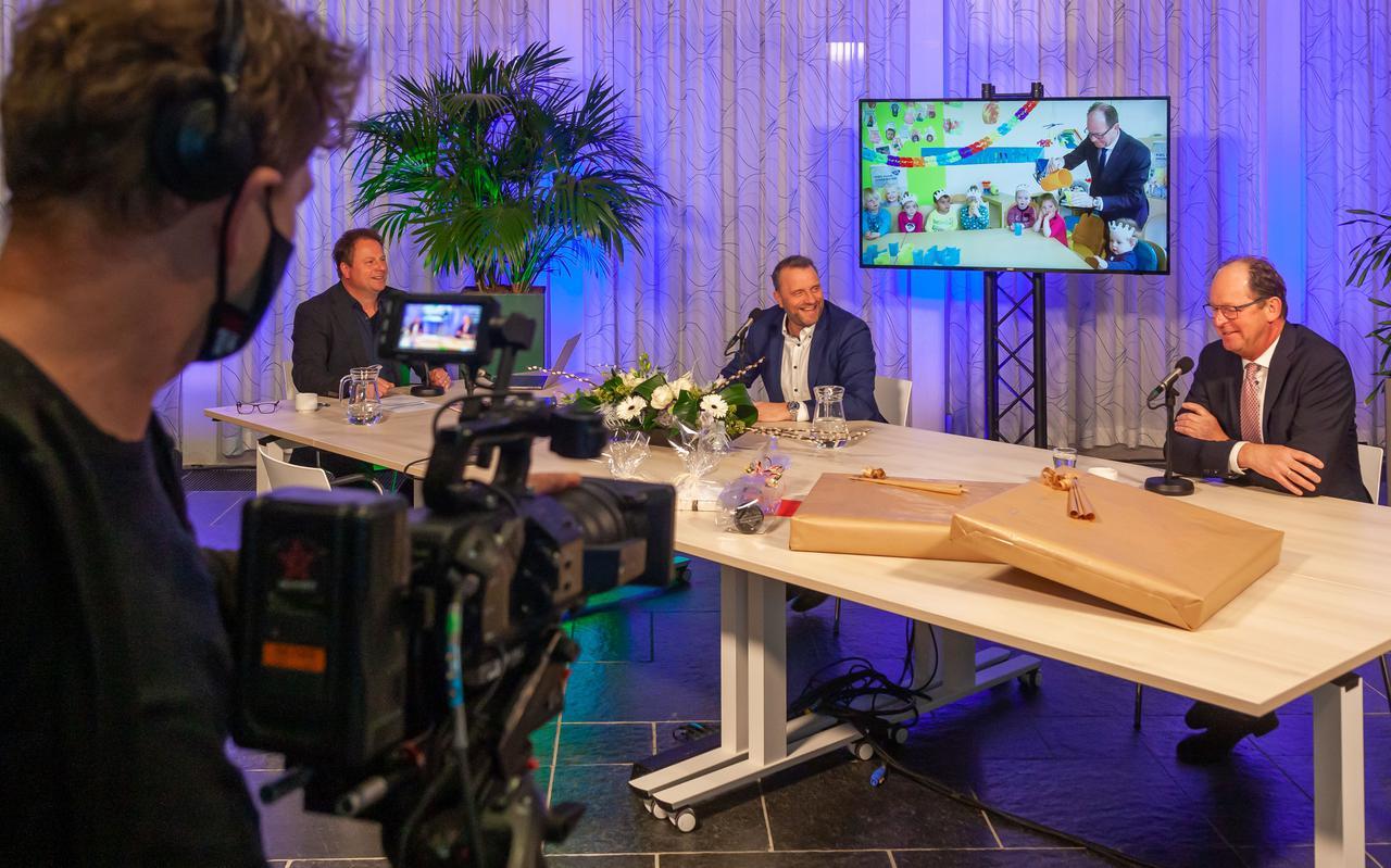 De oud-wethouders Erik Giethoorn en Gert Vos (rechts) nemen digitaal afscheid. Links presentator Serge Vinkenvleugel.
