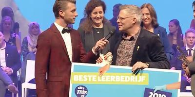 Praktijkopleider Cor Mulder van JC-Electronics nam de prijs in ontvangst. Links presentator Jan Versteegh. Op de achtergrond minister Ingrid van Engelshoven en directievoorzitter Hannie vlug.