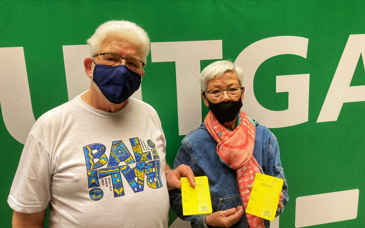 Roel Stäbler en Tineke de Charon de Saint Germain uit Delfzijl laten hun gele boekje met het felbegeerde coronavaccin-stempel zien.
