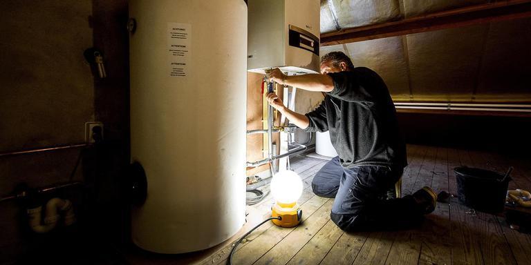 Een 'ketelman' aan het werk met een warmtepomp. Foto: ANP/Koen van Weel