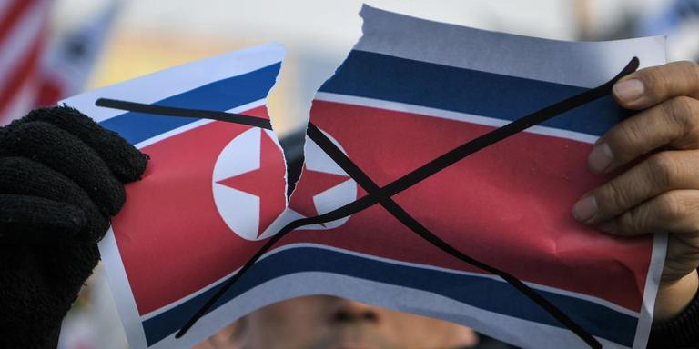 Een anti-Noord-Koreaanse demonstrant verscheurt een poster van de Noord-Koreaanse vlag bij het olympisch stadion voorafgaand aan de opening van de Olympische Spelen. Foto AFP/Ed Jones