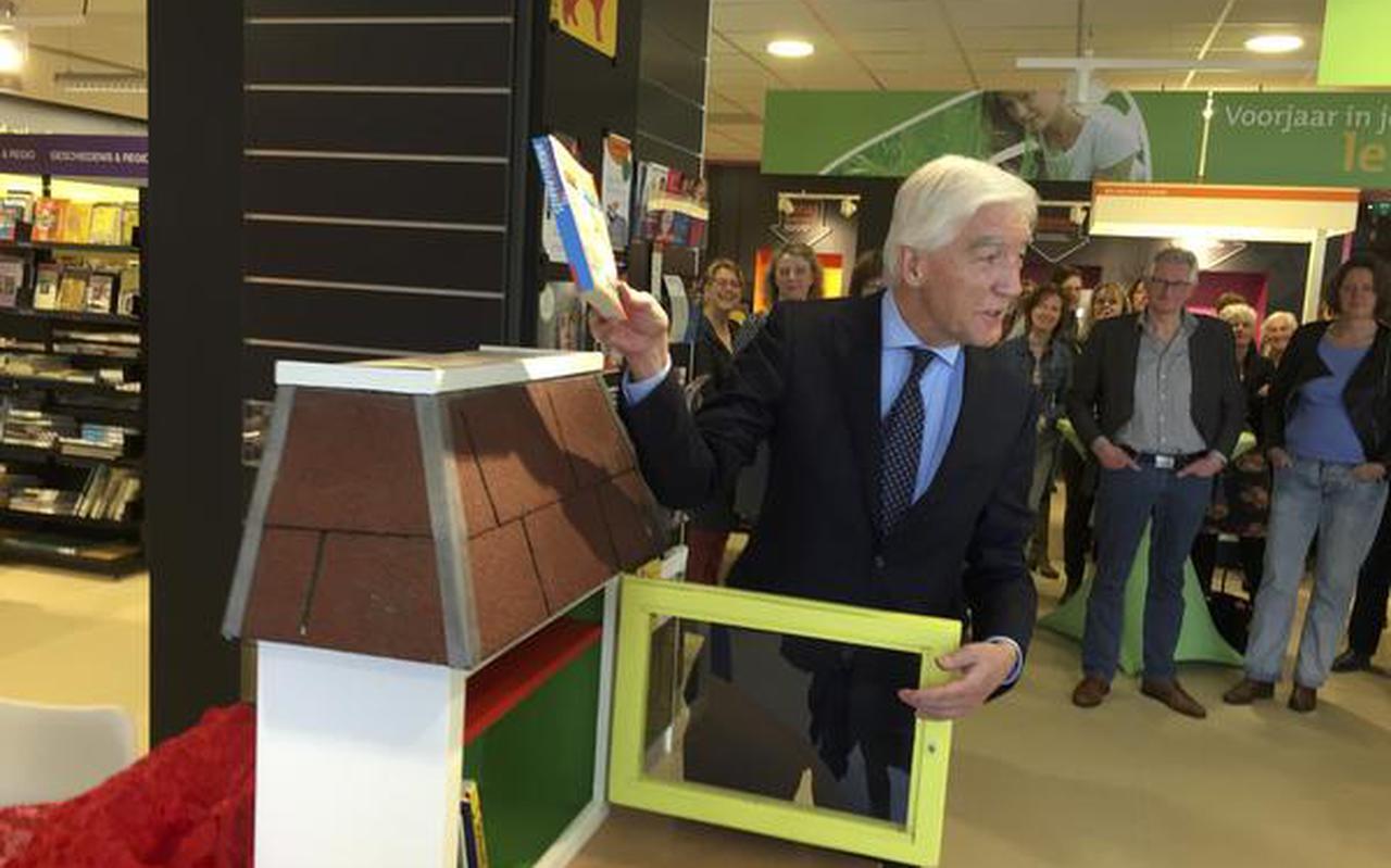 De Groningse CdK Max van den Berg tovert een boek tevoorschijn uit een speciale boekenkast die hij opende in de bibliotheek in Grootegast. FOTO DVHN
