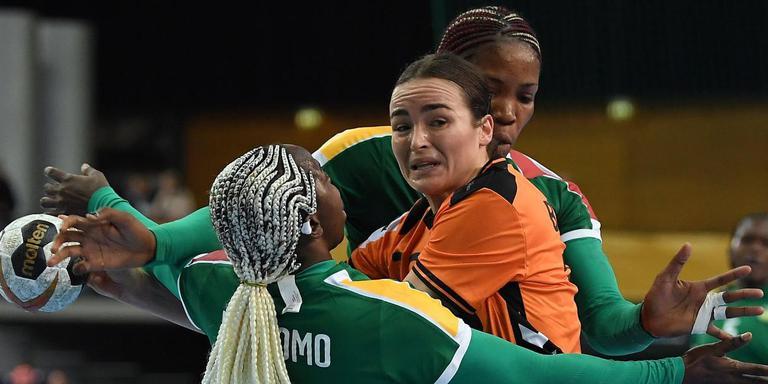 Yvette Broch in de mangel tussen twee speelsters van Kameroen. Foto AFP/dpa Hendrik Schmidt
