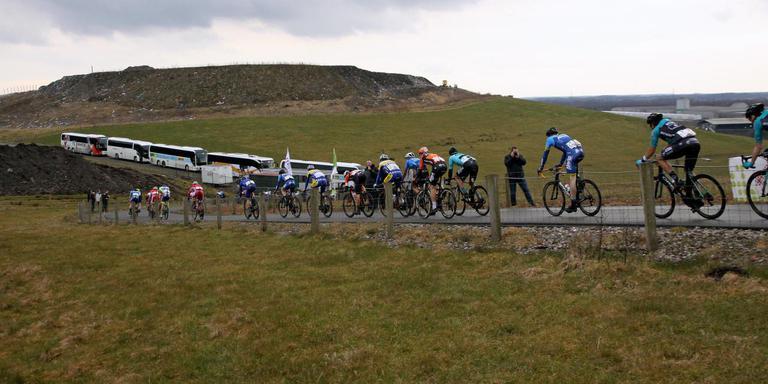 De renners duiken de VAM-berg af vlak voor de vele VIP-bussen langs.