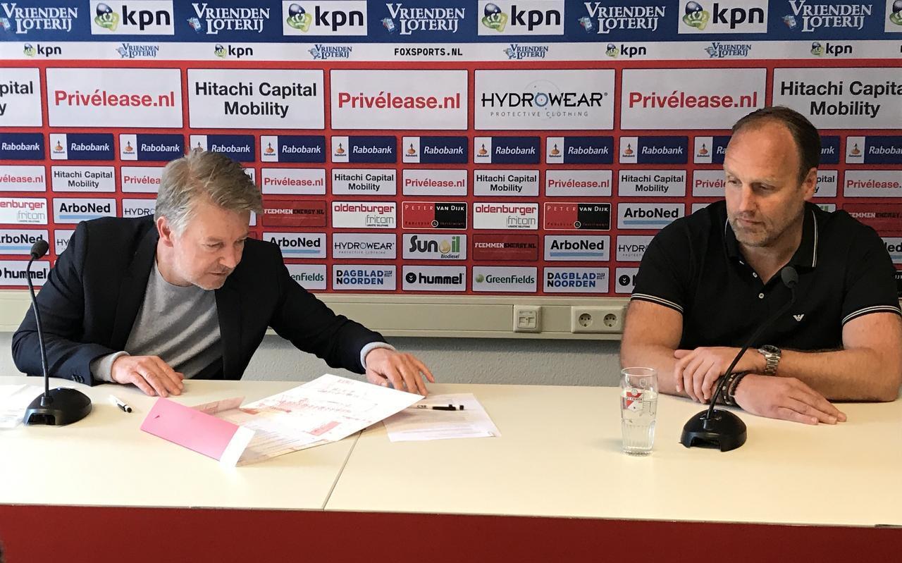 Voorzitter Ronald Lubbers neemt het contract met de verse handtekening van Dick Lukkien in ontvangst. De trainer heeft zich tot medio 2023 aan FC Emmen verbonden.