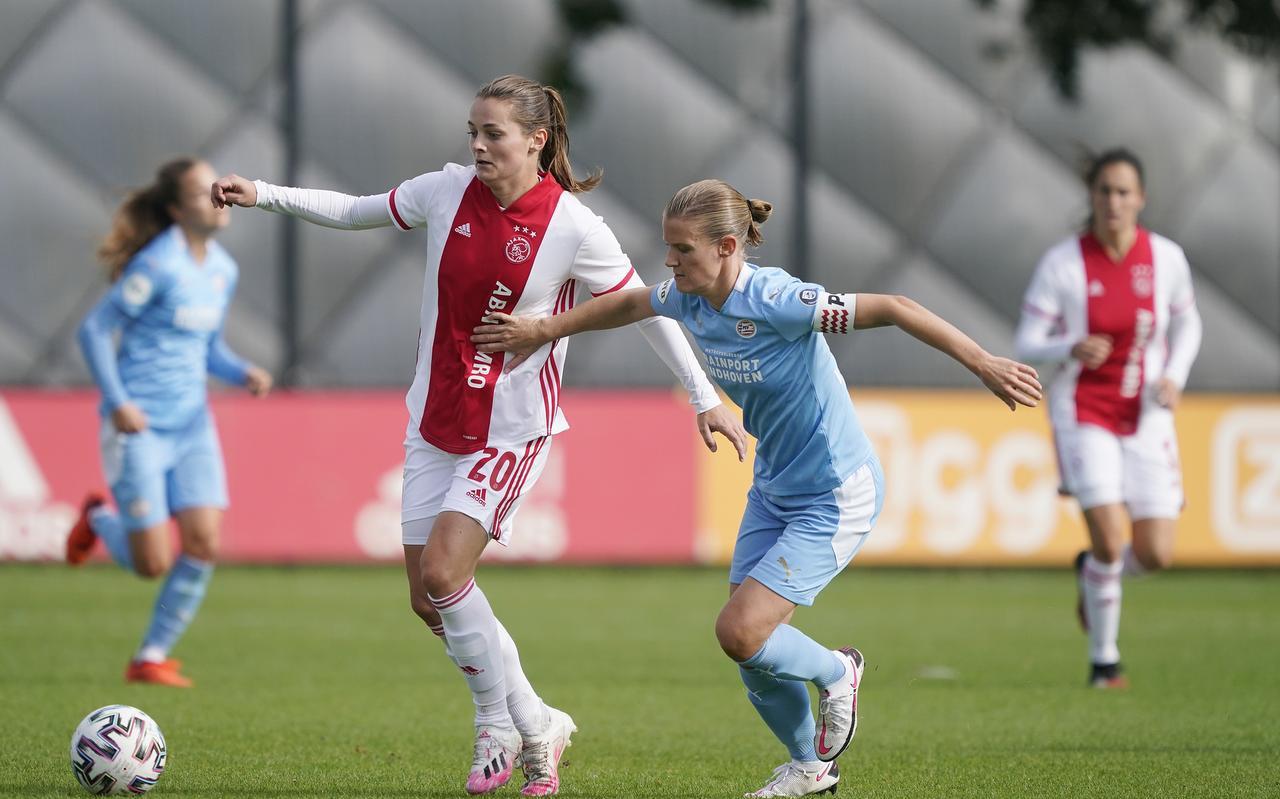 In de eredivisie vrouwen mag na een eerder verbod toch weer worden gevoetbald. Op de foto Eshly Bakker van Ajax in duel met Mandy van den Berg (rechts) van PSV Eindhoven.