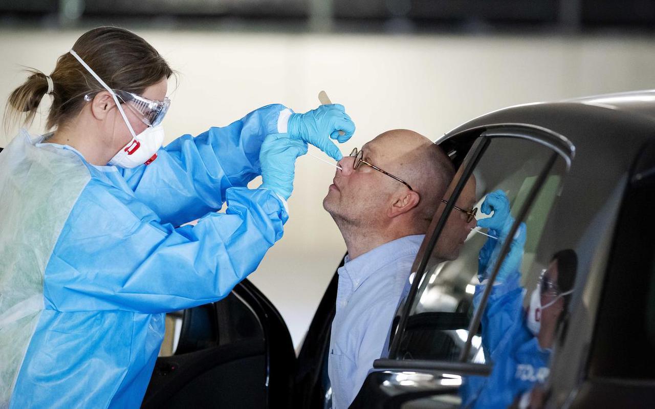 Een figurant laat zien hoe een bemonstering van neusslijm met een wattenstaafje geschiedt bij een drive-in van een GGD-testlocatie in Rotterdam.  FOTO ANP/ROBIN VAN LONKHUIJSEN