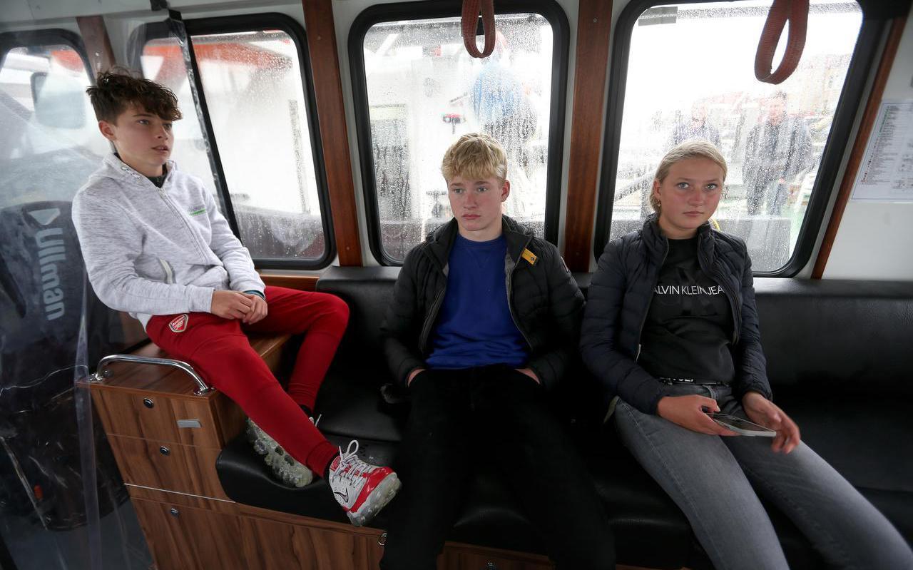 Etienne François, Micha Koning en Fleur Geertzen op het veerbootje dat hen 's morgens van Vlieland naar Terschelling brengt en 's middags weer terug.